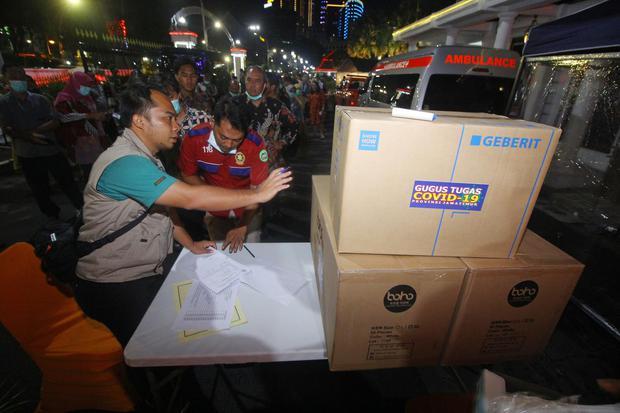 Sejumlah perwakilan dari rumah sakit mengantre untuk mendapatkan bantuan alat pelindung diri (APD) di Posko Penanganan dan Penanggulangan COVID-19 di Surabaya, Jawa Timur, Senin (23/3/2020). Pemprov Jawa Timur memberikan bantuan berupa APD kepada tenaga m