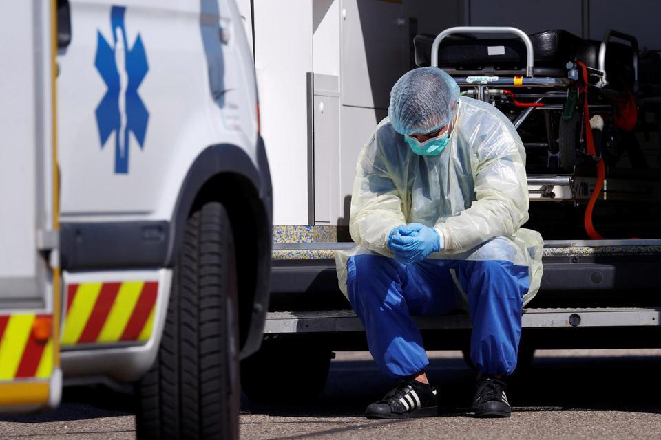 Christian Hartmann Petugas medis dengan alat pelindung diri beristirahat selama pemindahan pasien yang terinfeksi virus corona (COVID-19) dari Starsbourg menuju Jerman dan Swiss, Prancis, Senin (30/3/2020).