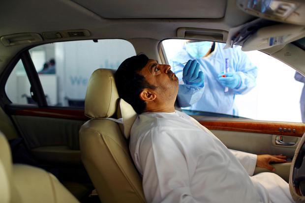 Ahmed Jadallah Petugas mengambil sampel uji swab pada seorang pria di Abu Dhabi, Uni Emirat Arab, Senin (30/3/2020). Uni Emirat Arab telah mengizinkan penggunaan vaksin Covid-19 secara darurat bagi petugas Kesehatan.