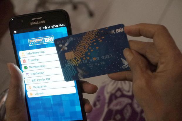 Seorang pensiunan PNS memperlihatkan kartu Automatic Teller Machine (ATM) milik Bank Rakyat Indonesia (BRI) yang baru diterimanya oleh petugas bank di Medan, Sumatera Utara, Rabu (1/4/2020).