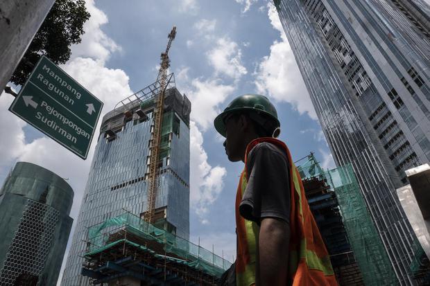 Ilustrasi, Pekerja melintas dengan latar belakang pembangunan gedung bertingkat di kawasan Kuningan, Jakarta, Jumat (3/4/2020). Bank Indonesia (BI) mengoreksi proyeksi pertumbuhan ekonomi Indonesia paling rendah 2,3 persen pada tahun ini yang akan ditopan