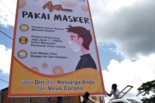 Pekerja memasang imbauan menggunakan masker di Syech Yusuf, Kendari, Sulawesi Tenggara, Selasa (7/4/2020). Pemerintah kota Kendari bekerja sama dengan pemilik billboard serta media advertising memasang imbauan kepada seluruh masyarakat menggunakan masker
