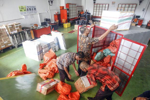 Petugas memilah paket kiriman barang di Kantor Pos, Cibinong, Bogor, Jawa Barat, Jumat (17/4/2020). Menurut petugas, dimasa penerapan Pembatasan Sosial Berskala Besar (PSBB), volume pengiriman paket pos khusus belanja online mengalami kenaikan rata-rata