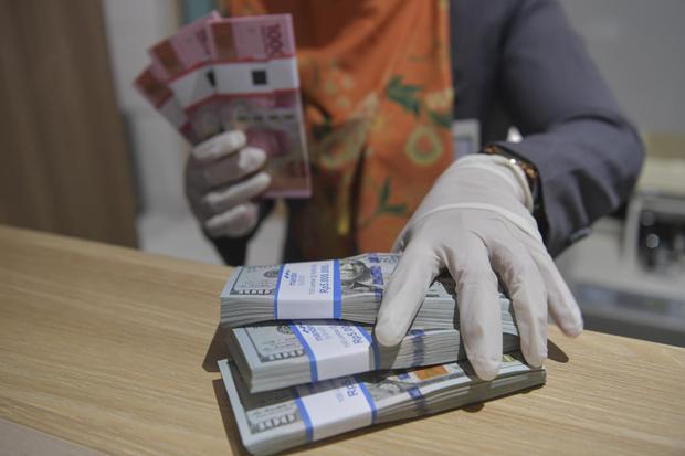 Ilustrasi, uang rupiah dan dolar AS. Nilai tukar rupiah melemah ke level Rp 14.590 per dolar AS karena pelaku pasar khawatir prospek pemulihan ekonomi terancam peningkatan kasus Covid-19 dan ketegangan hubungan AS-Tiongkok.
