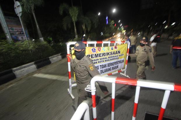 Petugas gabungan memasang pagar untuk menyekat jalan masuk ke dalam kota saat pemberlakuan jam malam di perbatasan Kota Banjarmasin, Kalimantan Selatan, Jumat (24/4/2020) malam. Saat pemberlakuan jam malam untuk mendukung Pembatasan Sosial Berskala Besar