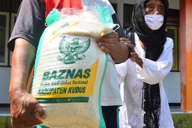 Warga membawa beras yang diterimanya saat pemberian bantuan di Kelurahan Wergu, Kudus, Jawa Tengah, Selasa (5/5/2020). Bantuan oleh BAZNAS (Badan Amil Zakat Nasional) sebanyak 155 ton beras kepada 15.500 warga yang tersebar di seluruh kabupaten itu untuk