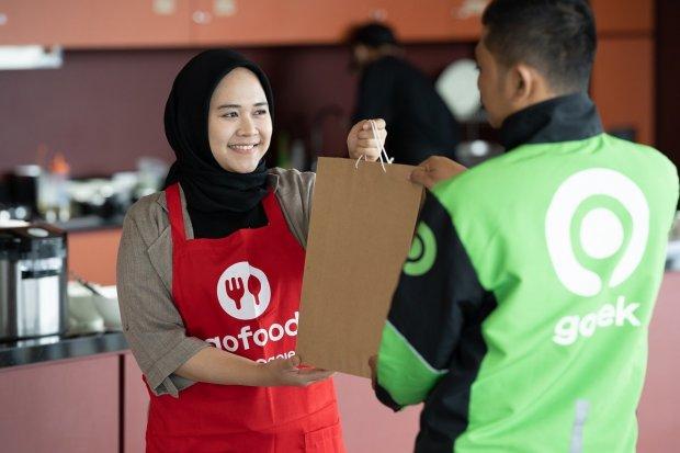 Gojek mendistribusikan paket makan gratis kepada mitra pengemudi lewat belasan ribu merchant GoFood.