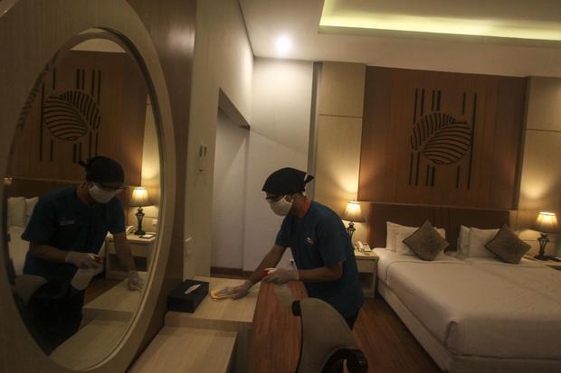 Ilustrasi, pekerja membersihan kamar dengan disinfektan. Perhimpunan Hotel dan Restoran Indonesia (PHRI) menyebutkan, tingkat okupansi hotel di akhir pekan naik 30% pada fase transisi PSBB.