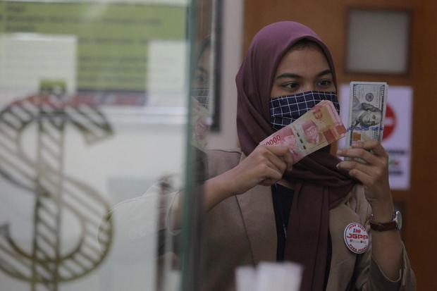 Karyawati menunjukkan mata uang rupiah dan dolar AS di salah satu gerai penukaran mata uang asing di Jakarta, Minggu (7/6/2020). Nilai tukar rupiah diperkirakan bakal melanjutkan tren penguatan di pekan kedua di Juni 2020 dimana pada penutupan Jumat (5/6)