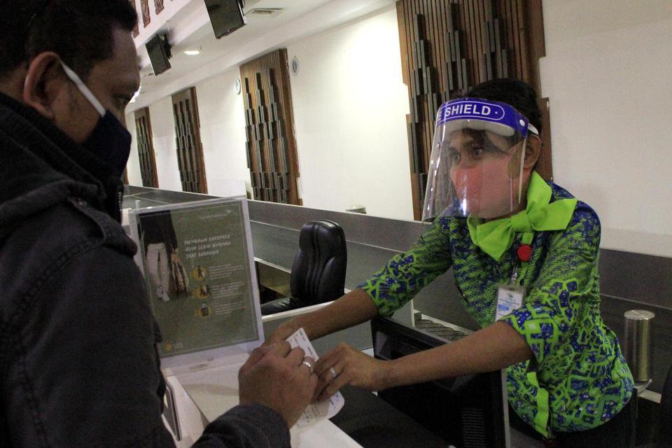 Petugas Garuda Indonesia saat memeriksa kelengkapan dokumen penumpang di bandara El Tari Kupang, NTT, Senin (8/6/2020). Pemerintah kembali membuka jalur penerbangan sebagai persiapan menyambut era normal baru.