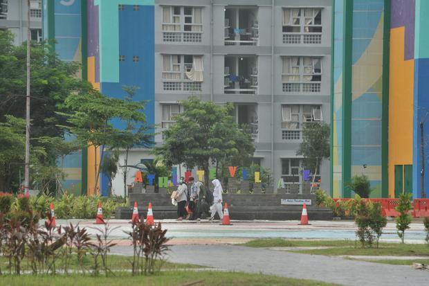 Petugas melintasi salah satu gedung wisma atlet Palembang, Sumsel, Senin (8/6/2020). Seiring dengan meningkatnya permintaan isolasi, Pemerintah Provinsi Sumsel berencana untuk menambah tiga tower wisma atlet untuk memenuhi kebutuhan tersebut.