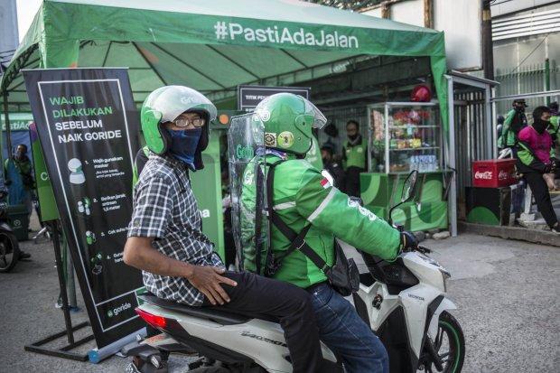 Pengemudi ojek online menggunakan pembatas mengangkut penumpang di Shalter Kawasan Stasiun Sudirman, Jakarta Pusat, Senin (8/6/2020). Pemerintah telah memperbolehkan ojek online mengangkut penumpang per tangga 8 Juni 2020 pada masa Transisi Fase I.