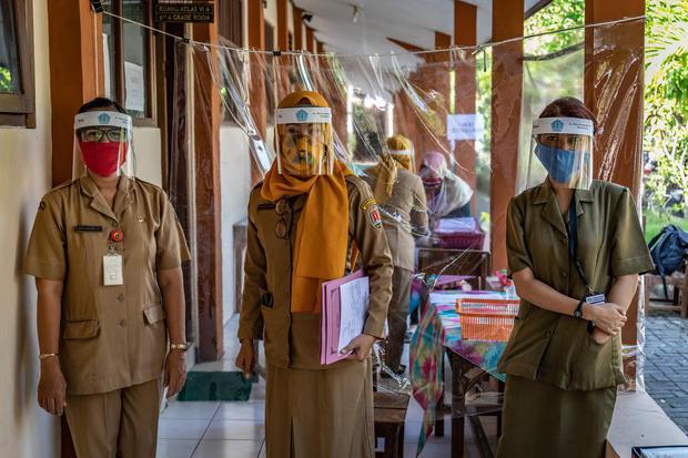 Panitia Penerimaan Peserta Didik Baru (PPDB) Tahun Pelajaran 2020/2021 mengenakan masker dan pelindung wajah di SDN Karangayu 02, Kelurahan Karangayu, Kota Semarang, Jawa Tengah, Senin (15/6/2020). tahun ajaran baru akan dimulai pada 13 Juli 2020.