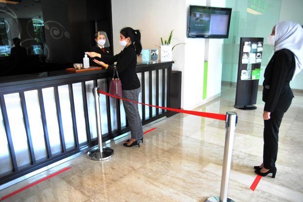 Tamu hotel antre dengan jaga jarak fisik di Hotel Santika, Kota Bogor, Jawa Barat, Selasa (16/6/2020). Meskipun tingkat hunian hotel tersebut masih rendah berkisar 20 hingga 30 persen namun manajemen hotel tetap menerapkan protokol kesehatan ketat untuk s