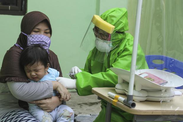 Seorang dokter mengenakan Alat Pelindung Diri (APD) saat melakukan imunisasi kepada anak di Puskesmas Cisalak Pasar, Depok, Jawa Barat, Rabu (24/6/2020). Ikatan Dokter Anak Indonesia (IDAI) mengajak orang tua agar tidak menunda pemberian imunisasi pada an
