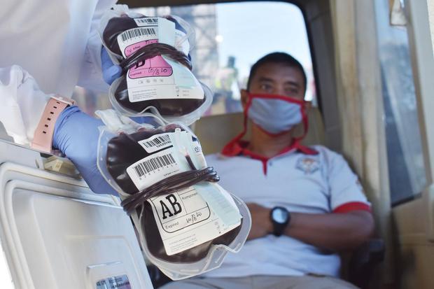 Petugas Unit Tranfusi Darah Palang Merah Indonesia (PMI) menunjukkan kantong berisi darah dari pendonor saat berlangsung donor darah di dalam mobil Unit Donor Darah di areal Hari Bebas Kendaraan Bermotor atau Car Free Day (CFD) Kota Madiun, Jawa Timur, Mi
