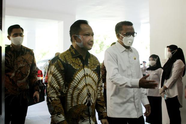 Gubernur Sulawesi Selatan Nurdin Abdullah (berkemeja putih) mendampingi Menteri Dalam Negeri Tito Karnavian saat melakukan kunjungan kerja di Makassar, Sulawesi Selatan, Rabu (8/7/2020).
