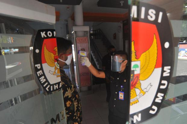 Petugas menggunakan pelindung wajah mengecek suhu tubuh staf yang datang di Kantor Komisi Pemilihan Umum (KPU) Sumatera Barat, di Padang, Jumat (10/7/2020). KPU pusat menyiapkan perlengkapan APD dan fasilitas kesehatan untuk panitia dan peserta pemilu di