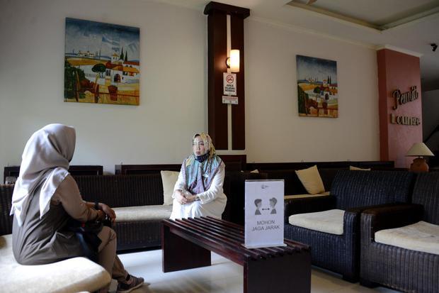 Petugas hotel (kanan) mengenakan alat pelindung wajah (Face shield) dan masker berbincang dengan seorang tamu di Hotel Oasis, Banda Aceh, Aceh, Rabu (15/7/2020). Untuk membangkitkan kembali sektor pariwisata dan ekonomi kreatif yang terdampak pandemi COVI