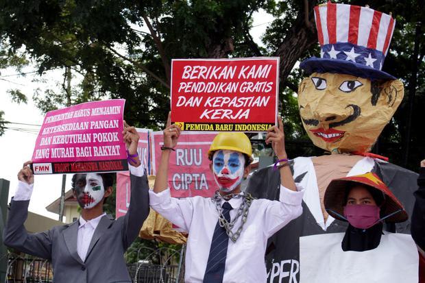 Demonstran membawa poster saat melakukan aksi unjuk rasa di depan Kantor DPRD Sulsel di Makassar, Sulawesi Selatan, Kamis (16/7/2020). Mereka menuntut DPR membatalkan Rancangan Undang-Undang (RUU) Omnibus Law Cipta Kerja serta mendesak pemerintah untuk me