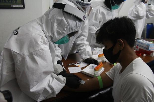 Petugas medis mengambil sampel darah pesepak bola Arema FC, Titan Agung Bagas (kanan) saat tes cepat (rapid test) COVID-19 di Kantor Arema FC di Malang, Jawa Timur, Jumat (17/7/2020). Manajemen Arema FC mengadakan tes diagnostik cepat kepada seluruh pemai