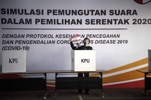 Warga menunjukkan contoh surat suara saat simulasi pemungutan suara pemilihan serentak 2020 di Jakarta, Rabu (22/7/2020). Simulasi tersebut digelar untuk memberikan edukasi kepada masyarakat terkait proses pemungutan dan penghitungan suara Pilkada serenta
