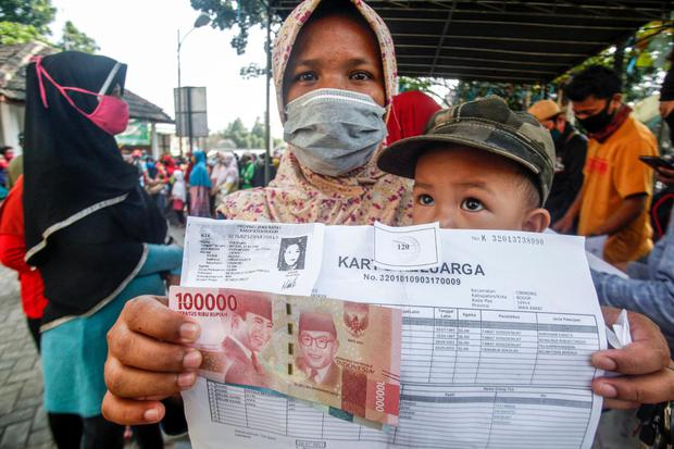 Warga menerima bantuan sosial (Bansos) tahap dua Provinsi Jawa Barat, di Kelurahan Harapan Jaya, Cibinong, Bogor, Jawa Barat, Kamis (23/7/2020). Pemerintah Provinsi Jawa Barat menyatakan penyaluran bansos tahap dua ini menyasar 1.392.407 Keluarga Rumah