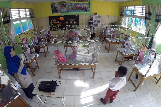 Sejumlah murid mengikuti kegiatan belajar secara tatap muka menggunakan meja bersekat plastik, di Sekolah Dasar Negeri (SDN) 09 Pasar Pandan Airmati (PPA), Kec. Tanjung Harapan, Kota Solok, Sumatera Barat, Jumat (24/7/2020). Sekolah tersebut memberlakukan