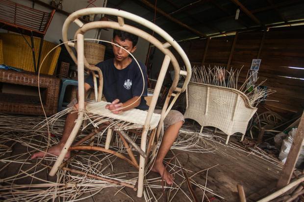 Perajin menyelesaikan pesanan di sentra kerajinan rotan di Jalan George Obos, Palangkaraya, Kalimantan Tengah, Kamis (30/7/2020). Kementerian Koperasi dan UKM (Kemenkop UKM) mengatakan realisasi belanja dana program Pemulihan Ekonomi Nasional (PEN) kepada