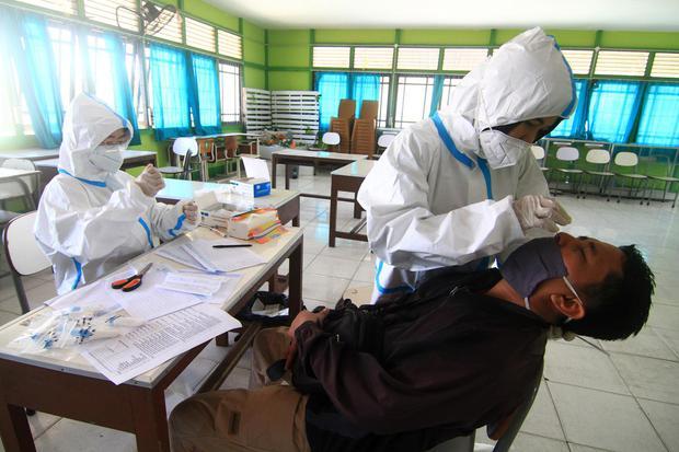 Ilustrasi, petugas kesehatan melakukan tes usap (swab test). Satgas Penanganan Covid-19 mencatat tingkat positif virus corona Indonesia tiga kali lipat di atas rekomendasi WHO.
