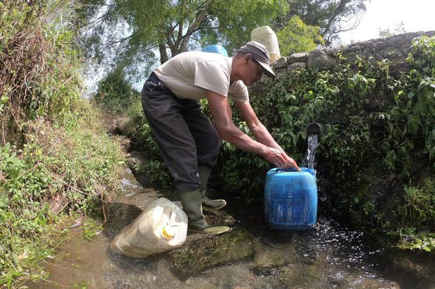 Seorang warga Sungai Jambu menampung air yang mengalir dari sumber mata air di kaki Gunung Kerinci, Kayu Aro Barat, Kerinci, Jambi, Minggu (2/8/2020). Beberapa desa yang wilayahnya belum mendapatkan layanan Perusahaan Daerah Air Minum (PDAM) di daerah itu