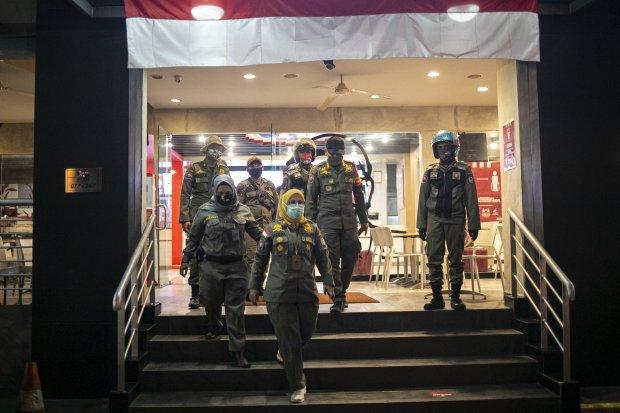 Penjual menutup tokonya saat dilakukan sosialisasi pembatasan jam malam di sepanjang Jalan Margonda, Depok, Jawa Barat, Senin (31/8/2020).