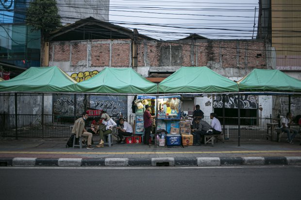 Warga memakan hidangan pedagang kaki lima Kawasan Stasiun Sudirman, Jakarta Pusat, Senin (14/9/2020). Selain itu, penerapan PSBB kali ini tak memperbolehkan aktivitas makan di tempat (dine in) kepada pengunjung restoran atau rumah makan. Aktivitas jual be