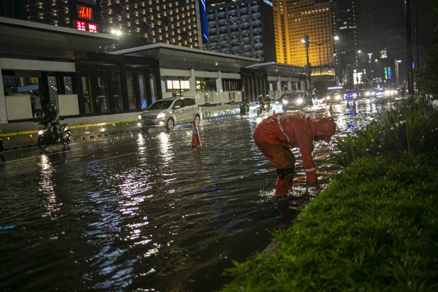 Petugas membersihkan saluran air di Kawasan Jalan Sudirman-Thamrin, Jakarta Pusat, Senin (21/9/2020). Hujan deras yang mengguyur sebagian wilayah ibu kota menyebabkan beberapa titik di Jakarta tergenang banjir hingga 50 centimeter.