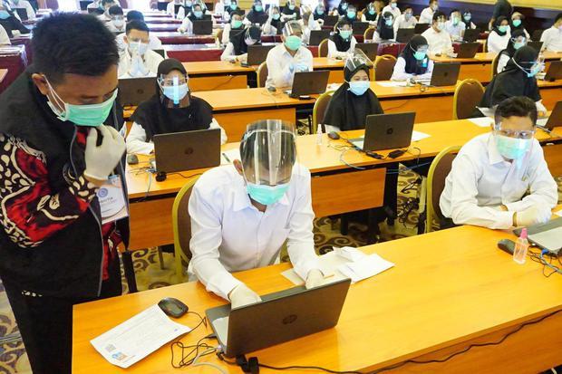 Petugas memandu peserta melakukan proses login komputer ujian Seleksi Kemampuan Bidang (SKB) di program penjaringan CPNS 2019 di Tulungagung, Jawa Timur, Rabu (30/9/2020). Ujian seleksi CPNS 2019 yang diikuti 1.505 peserta itu digelar dengan menerapkan pr