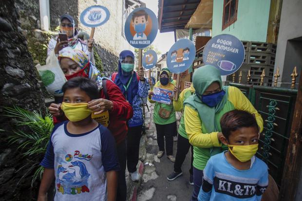 Petugas puskesmas memakaikan masker kepada seorang anak saat sosialisasi gerakan 3M (memakai masker, mencuci tangan, dan menjaga jarak) di kawasan pemukiman warga Tanah Sareal , Kota Bogor, Jawa Barat, Kamis (1/10/2020). Sosialisasi gerakan 3M di kawasan
