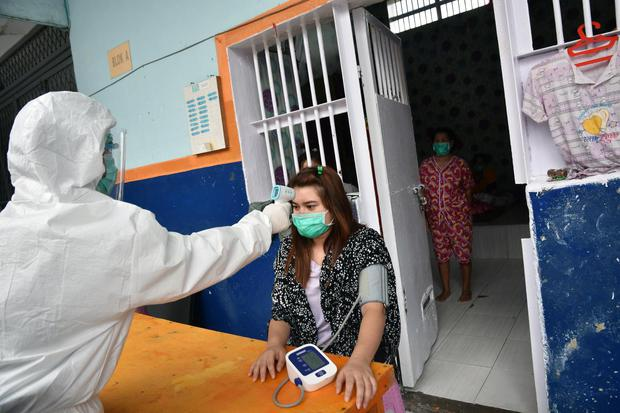 Petugas Lembaga Pemasyarakatan (Lapas) Perempuan Kelas IIA Pekanbaru mengenakan alat pelindung diri saat memeriksa kesehatan warga binaan yang positif COVID-19, di Kota Pekanbaru, Riau, Kamis (1/10/2020). Lapas Perempuan Pekanbaru kewalahan akibat klaster