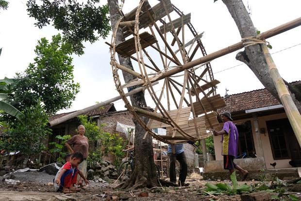 Warga menggunakan manfaat kincir air tradisional berbahan bambu di Kalinegoro, Magelang, Jateng, Minggu (4/10/2020). Kincir air bambu atau Jinontrot biasa digunakan petani setempat saat musim kemarau untuk menaikkan air dari sungai ke persawahan yang leta