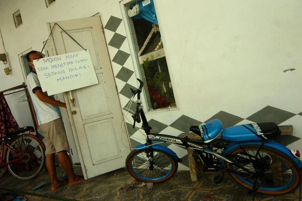 Seorang warga positif COVID-19 berada di dalam rumahnya di Kelurahan Kejambon, Tegal, Jawa Tengah, Rabu (28/10/2020). Warga tersebut beserta lima anggota keluarganya melakukan isolasi mandiri karena positif COVID-19, sehingga para tetangga di daerah terse