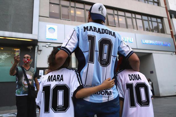 Matias Baglietto Penggemar pemain sepakbola Argentina Diego Maradona, Walter Rotundo dan anak perempuan kembarnya Mara dan Dona, yang diberi nama mirip Maradona, berpose untuk foto di luar klinik dimana Maradona melakukan operasi otak, di Olivos, di ping