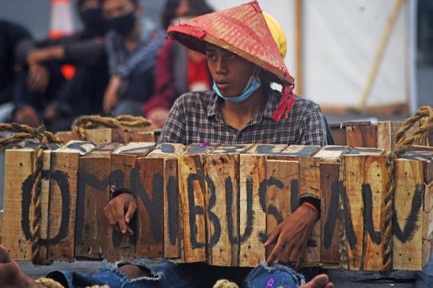 Mahasiswa yang tergabung dalam Aliansi Mahasiswa Banten (AMB) menggelar aksi teatrikal saat berunjuk rasa menolak Omnibus Law Undang-undang Cipta Kerja di Alun-alun Serang, Selasa (10/11/2020).