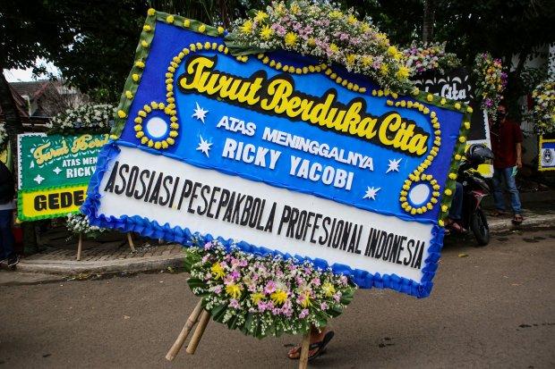 Seorang warga mengangkat karangan bunga di rumah duka mantan Timnas sepak bola Indonesia Ricky Yacobi di Pondok Ranji, Kota Tangerang Selatan, Banten, Sabtu (21/11/2020). Ricky Yacobi meninggal dalam usia 57 tahun karena serangan jantung saat bermain sepa