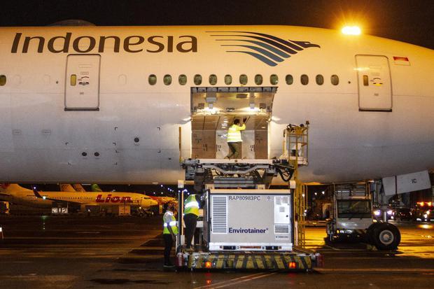Petugas menurunkan kontainer berisi vaksin COVID-19 saat tiba di Bandara Soekarno-Hatta, tangerang, Banten, Minggu (6/12/2020). Sebanyak 1,2 juta dosis vaksin COVID-19 buatan perusahaan farmasi Sinovac, China, tiba di tanah air untuk selanjutnya akan dipr
