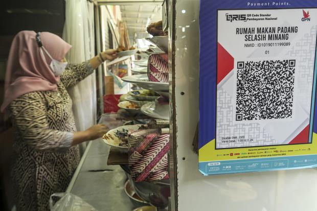 Sebuah kode batang (QR barcode) transaksi nontunai terpasang di rumah makan, di Jakarta, Jumat (18/12/2020). Bank Indonesia (BI) memperpanjang kebijakan gratis biaya transaksi nontunai yang dibebankan ke toko (Merchant Discount Rate/MDR) alias nol persen
