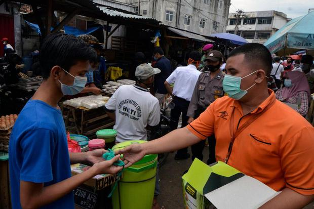 Personel Satgas BUMN Lampung membagikan masker kepada warga di Pasar Pasir Gintung dan Bambu Kuning Bandar Lampung, Lampung, Selasa (29/12/2020). Pembagian masker tersebut dalam rangka sosialisai penerapan protokol kesehatan untuk masyarakat dan pedagang