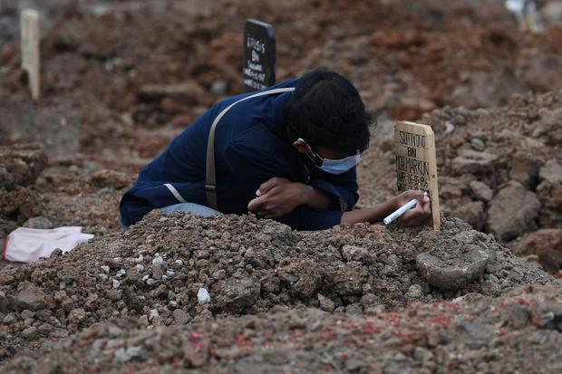 Seorang warga menulis nama di nisan kerabatnya yang dimakamkan dengan protokol COVID-19 di TPU Tegal Alur, Jakarta, Selasa (29/12/2020). Pemprov DKI Jakarta menyiapkan lahan pemakaman di Rorotan sebagai antisipasi penuhnya TPU khusus COVID-19 di Pondok Ra