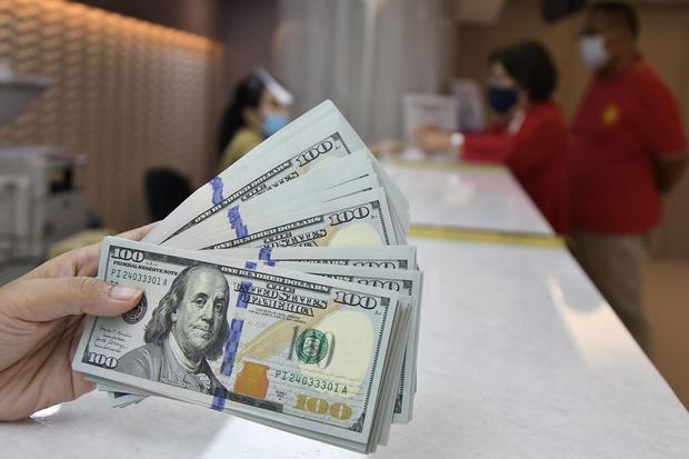 Karyawan menunjukkan uang dolar Amerika Serikat (AS) di tempat penukaran valuta asing, Jakarta, Rabu (6/1/2021). Nilai tukar rupiah menguat 20 poin (0,14 persen) terhadap mata uang Negeri Paman Sam dan ditutup pada level Rp 13.895 per dolar AS.