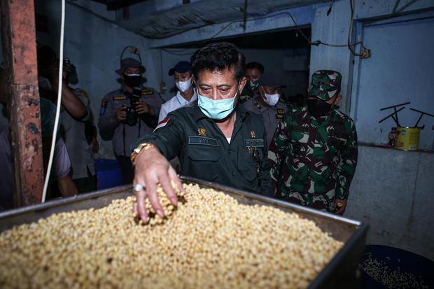 Menteri Pertanian Syahrul Yasin Limpo meninjau tempat produksi tempe saat operasi stabilitas harga kedelai di Semanan, Jakarta, Kamis (7/1/2021). Dalam operasi pasar tersebut, kedelai dijual ke perajin seharga Rp8.500 per kilogram dan diupayakan bertahan