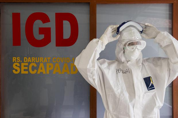 Petugas kesehatan menggunakan alat pelindung diri sebelum memasuki ruang isolasi hijau Rumah Sakit darurat COVID-19 di Sekolah Calon Perwira Angkatan Darat (Secapa AD), Hegarmanah, Bandung, Jawa Barat, Selasa (12/1/2021). Rumah Sakit darurat COVID-19 Seca
