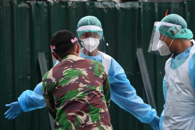 Seorang prajurit TNI AD memeriksa petugas kebersihan yang mengenakan pakaian pelindung diri sebelum memasuki Rumah Sakit Lapangan Kogabwilhan II Jalan Indrapura, Surabaya, Jawa Timur, Selasa (12/1/2021). Berdasarkan data Satuan Tugas Penanganan COVID-19 p